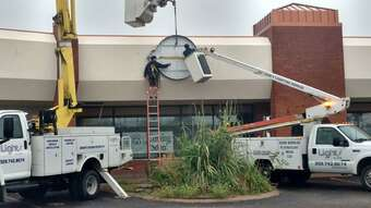 H&H Lighting Maintenance truck being used to repair an exterior pole light in a parking lot
